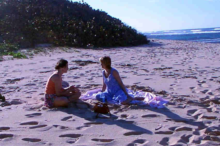 Two women share a holistic healing process during a Vibrational Healing Workshop on the beach in Hawaii
